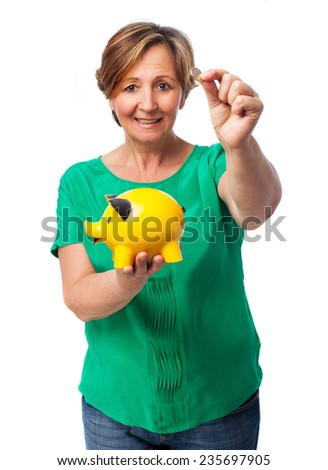 portrait of a happy mature woman with her piggy bank