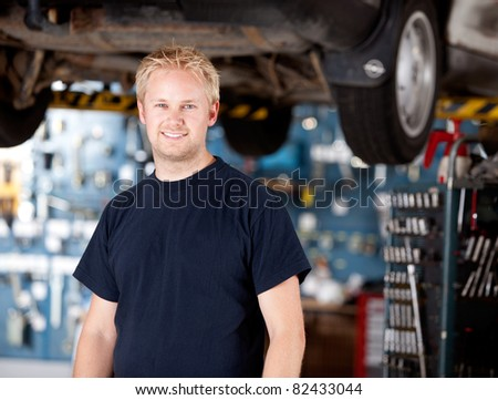 Portrait of a happy mchanic looking at the camera in garage - stock photo