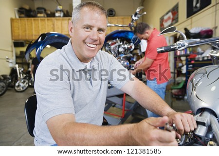 Portrait of a happy mechanic repairing a motorcycle with his coworker in the background