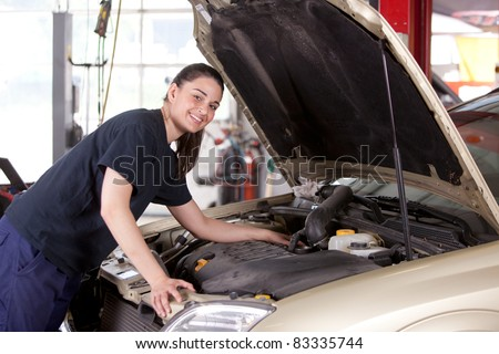 Portrait of a happy mechanic woman working on a car in an auto repair shop - stock photo