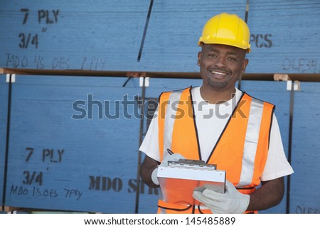Portrait of a happy mid-adult man working in warehouse - stock photo