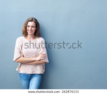 Portrait of a happy mid adult woman smiling with arms crossed on gray background - stock photo