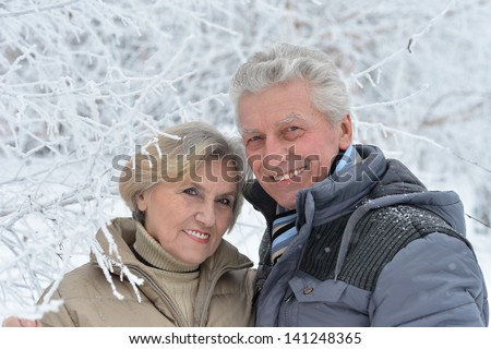 portrait of a happy middle-aged couple on a walk in winter - stock photo