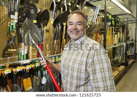 Portrait of a happy middle-aged man holding shovel in hardware store - stock photo