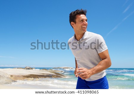 Portrait of a happy middle aged man walking on the beach - stock photo
