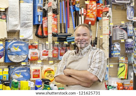 Portrait of a happy middle-aged salesperson with arms crossed in hardware store - stock photo