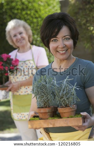 Portrait of a happy middle aged woman carrying potted plants with mother standing in the background - stock photo