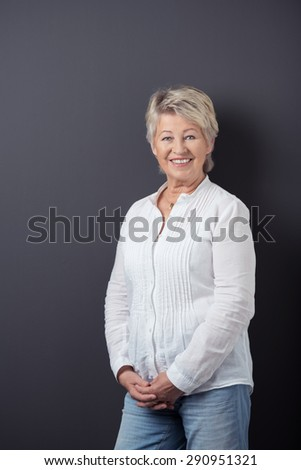 Portrait of a Happy Middle Aged Woman in Casual Shirt and Jeans, Leaning Against Gray Wall Background and Smiling at the Camera. - stock photo