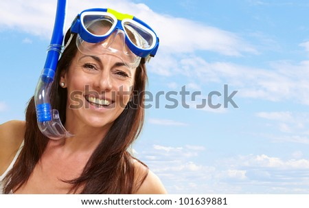 portrait of a happy middle aged woman wearing snorkel and goggles against a blue sky