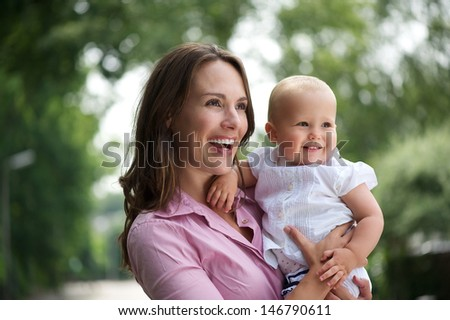 Portrait of a happy mother and baby laughing together in the park - stock photo