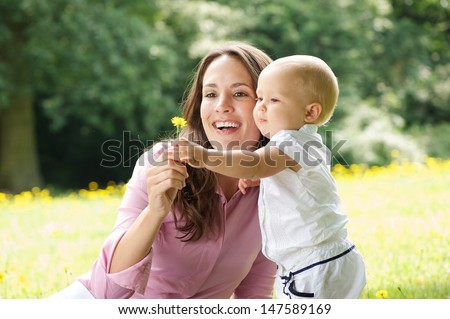 Portrait of a happy mother and child holding flower in the park - stock photo