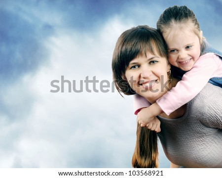 Portrait of a happy mother and daughter on the blue sky - stock photo