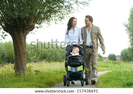 Portrait of a happy mother and father walking with baby in pram - stock photo