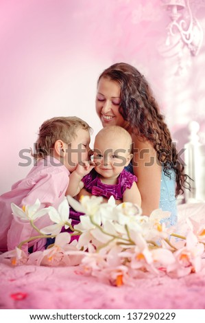 Portrait of a happy mother and her children boy and girl sitting on a bed smiling and kissing