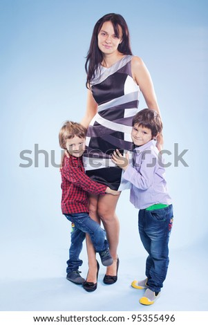 Portrait of a happy mother and her children in studio - stock photo