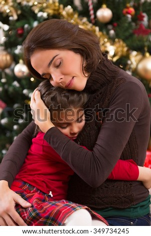 Portrait of a happy mother and her cute little daughter embracing in front of the Christmas tree - stock photo