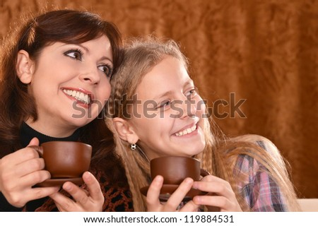 portrait of a happy mother and little girl drinking tea - stock photo