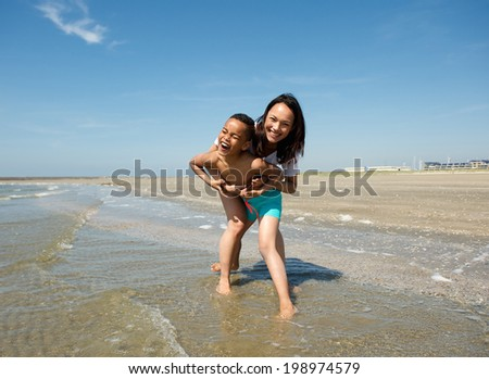 Portrait of a happy mother and son playing at the beach - stock photo