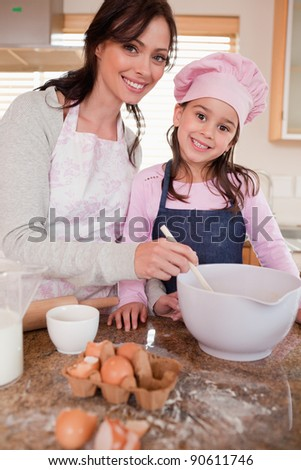 Portrait of a happy mother baking with her daughter in a kitchen - stock photo