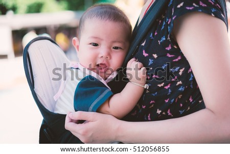 Portrait of a happy mother holding baby in Baby Carriers