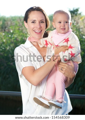 Portrait of a happy mother holding beautiful baby outdoors