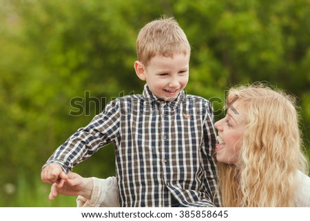 Portrait of a happy mother hugging her son - stock photo