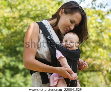 Portrait of a happy mother kissing baby on the head - stock photo