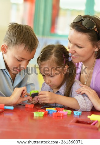 Portrait of a happy mother playing with her children - stock photo