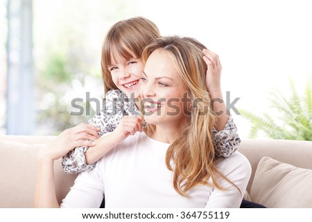 Portrait of a happy mother sitting in living room with her cutie daughter while having fun.  - stock photo