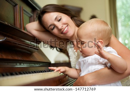Portrait of a happy mother smiling as baby plays piano  - stock photo