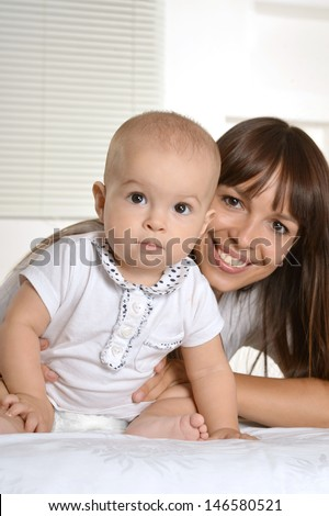 portrait of a happy mother with her baby on a light background