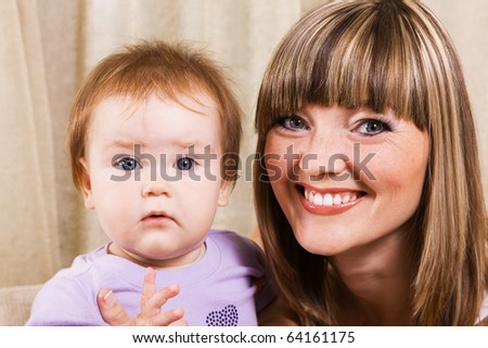 Portrait of a happy mother with lovely little daughter at home - stock photo