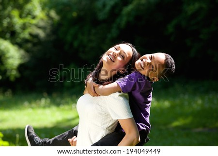 Portrait of a happy mother with son enjoying piggyback ride outdoors - stock photo