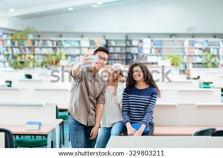 Portrait of a happy multi ethnic students making selfie photo on smartphone in the university library - stock photo