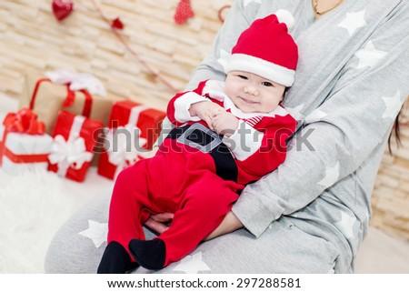 portrait of a happy newborn baby lying in Santa - stock photo
