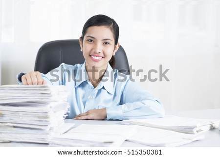 Portrait of a happy office worker with a bunch of documents at the table.