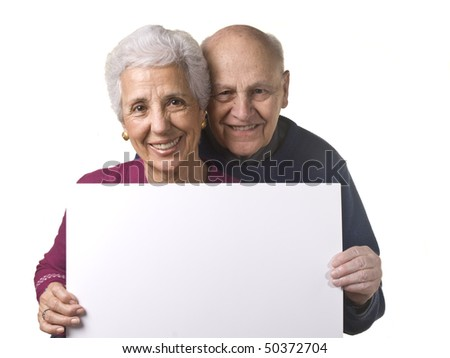 Portrait of a happy older couple holding blank billboard against white background - stock photo