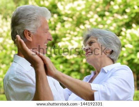 portrait of a happy older couple on a walk in the park in spring - stock photo