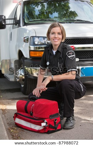 Portrait of a happy paramedic kneeling by a portable oxygen unit and ambulance - stock photo
