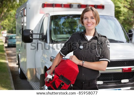 Portrait of a happy paramedica carrying a portable oxygen unit - stock photo