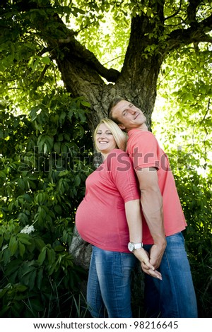 Portrait of a happy pregnant couple in jeans and pink t-shirts standing back to back.