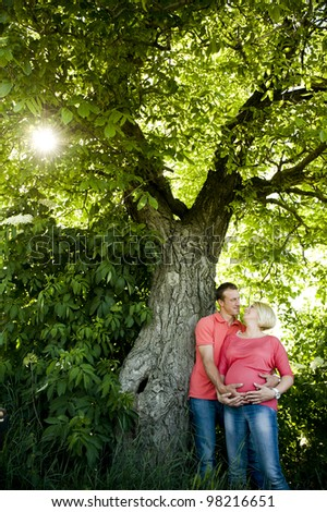 Portrait of a happy pregnant couple in jeans and pink t-shirts standing next to a walnut tree.