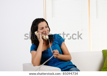 Portrait of a  happy pretty young woman talking on phone. - stock photo