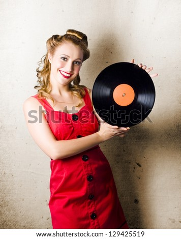 Portrait Of A Happy Rockabilly Music Girl Holding Retro Vinyl Record Lp On Grunge Background - stock photo