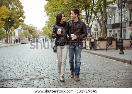 Portrait of a happy romantic couple with coffee walking outdoors in old european city - stock photo