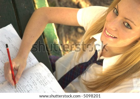 Portrait of a happy school girl doing her home work in a park. - stock photo