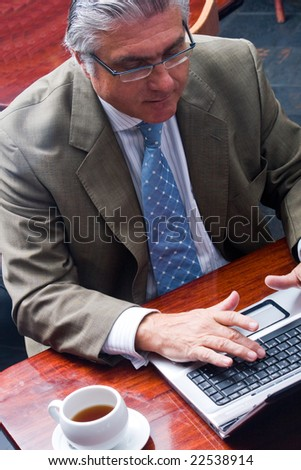 Portrait of a happy senior business man working on his laptop in a cafe - stock photo