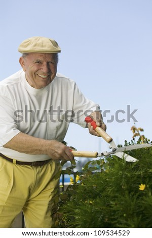 Portrait of a happy senior Caucasian man pruning plants with shears - stock photo