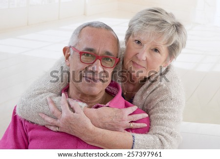 Portrait of a happy senior couple embracing and looking at camera - stock photo