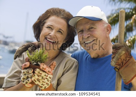 Portrait of a happy senior couple gardening together - stock photo